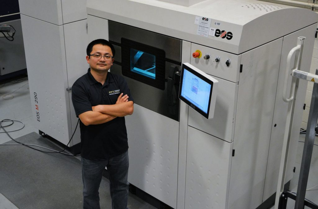 Dr. Xiong in the Swanson School's ANSYS Additive Manufacturing Laboratory with an EOS industrial 3D printing machine. Photo via University of Pittsburgh