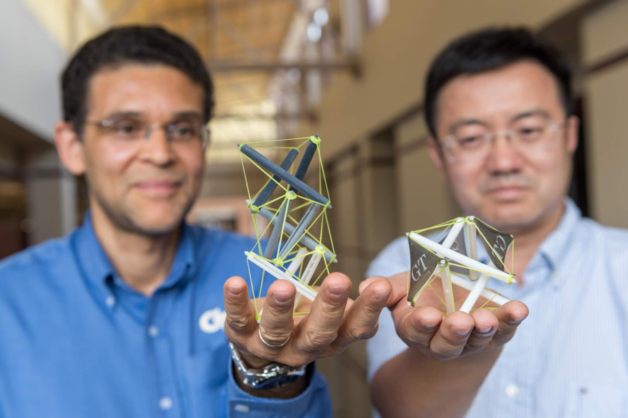 Georgia Tech professors Glaucio Paulino and Jerry Qi holding their tensegrity structures. Photo via Rob Felt/Georgia Tech.