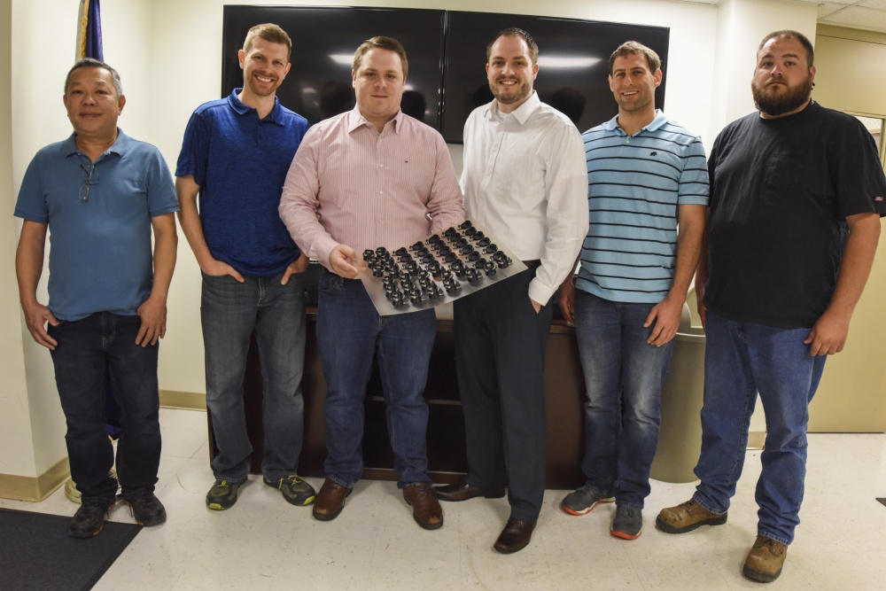 The team at NAVSEA's Additive Manufacturing Warfare Center Working Group and a batch of the 3D printed flip-top valves. U.S. Navy photo by Dustin Q. Diaz