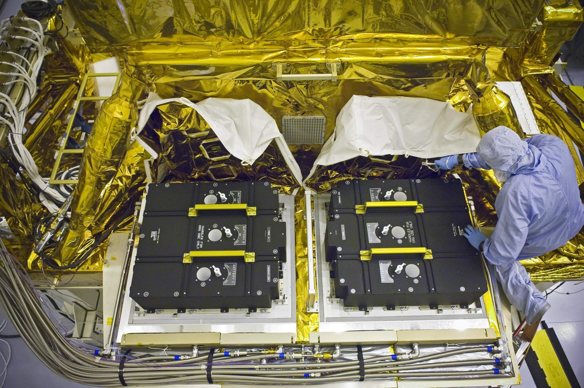 Technicians installing new batteries onto the Hubble Space Telescope. Photo via NASA.