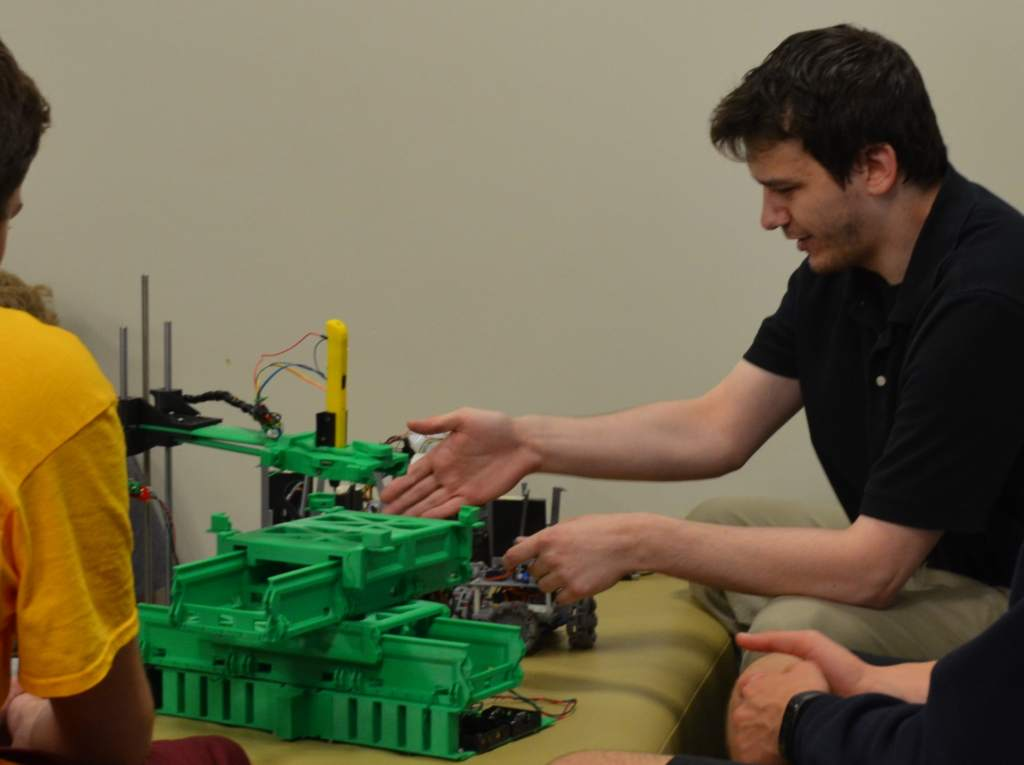 NDSU Software Engineering Ph.D. student Andrew Jones demonstrates the self-replicating robot's 3D printing capabilities. The robot is shown without its wheels and manipulator arm. Photo via Newswire