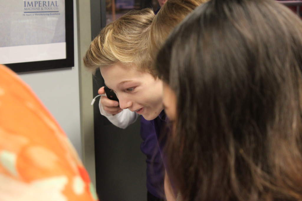 Student fascinated by a 3D metal printed component. Photo via Imperial Machine and Tool Co.