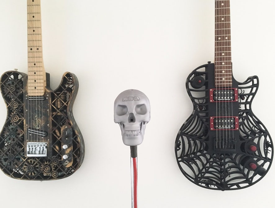 The Skeletor microphone with 3D printed guitars in the background. Image via Olaf Diegel.