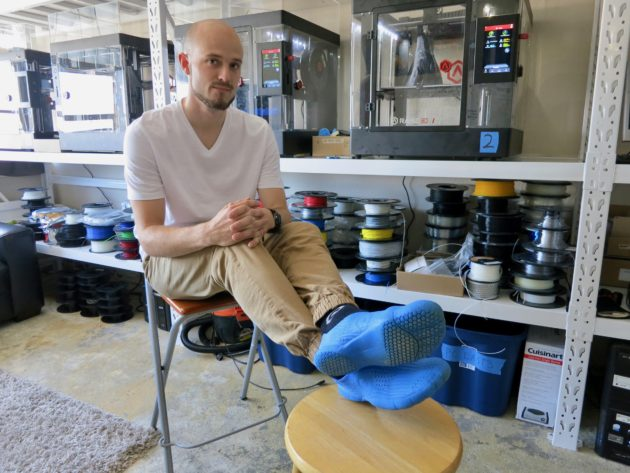 Founder Oliver Brossmann in his Biorunners while the next batch prints on the Raise3D N2 3D printers. Photo via Kurt Schlosser for GeekWire.