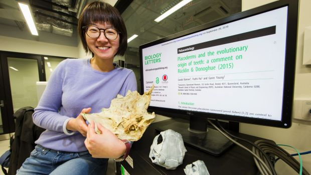 ANU's Yuzhi Hu hold the 3D printed modle of fossilized fish jaw. Photo by Stuart Hay