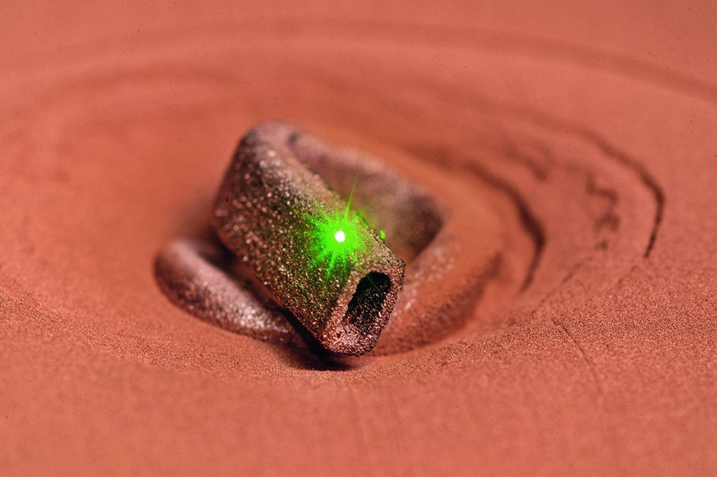 A 3D copper part emerges from a bed of powder in Fraunhofer ILT's project SLM in green. Photo by Fraunhofer ILT, Aachen, Germany.