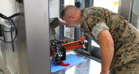 Gunnery Sgt. Doug McCue examines a 3D printer inside the Marines' expeditionary fabrication lab X-FAB. U.S. Marine Corps photo by Kailtin Kelly