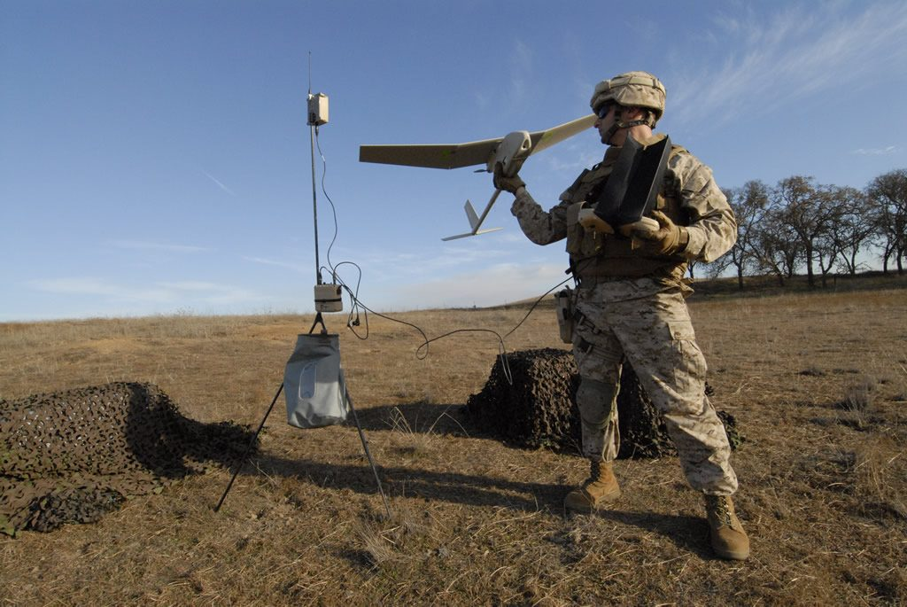 A marine prepares to hand launch a Raven drone/image via Defense Industry Daily