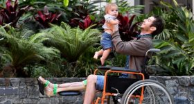 Reuben Lichter, the man with a 3D printed tibia, and his 8 month old son, transformed by a world first operation at Princess Alexandra Hospital, Brisbane. Photo via The Sydney Morning Herald