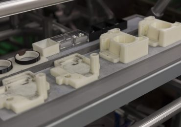 Stratasys 3D printed ABS fixtures on the Ricoh assembly line. Photo via Stratasys