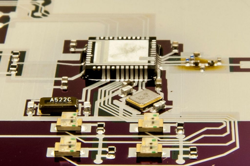 Aerosol jet printed part of a Bluetooth microprocessor. Photo via Draper Laboratory