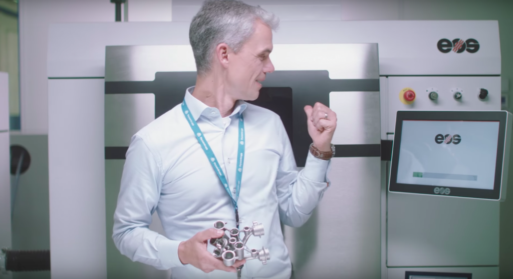 A team member shows off Thyssenkrupp's EOS M290 metal 3D printer. Photo via Youtube/Thyussenkrupp.