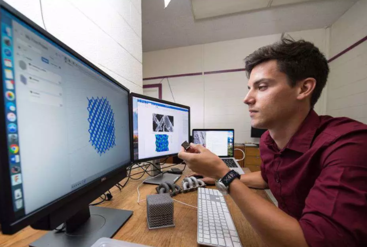 Edward Cyr examines a 3D rendering of a lattice structure. Photo via The Star Phoenix