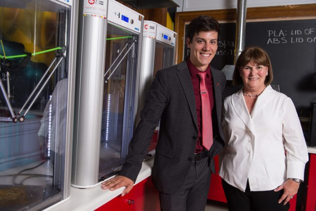 Cyr poses with a colleague next to a 3D metal printing machines after being awarded a McCain fellowship. Photo via Canadian Manufacturing.