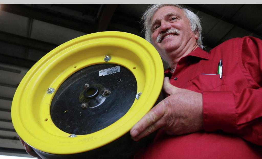 Robin Weisz (pronounced Wize) of Hurdsfield, N.D., shows off a yellow-colored display model of an insert that he and his friend, Ted Juhl, of Drayton, N.D., have developed to clean planter gauge wheels and save on tire wear for planters and air seeders. They had product to sell for the first time at Big Iron farm show in West Fargo in mid-September, but they will probably used commercially for the first time in the region next spring. Photo taken Sept. 15 at Big Iron, West Fargo, N.D. (Forum News Service/Agweek/Mikkel Pates)