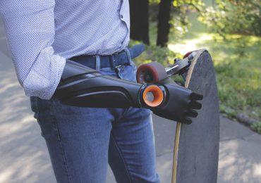 Piotr Sajdak holds a skateboard with his prosthetic arm. Photo via Glaze Prosthetics.