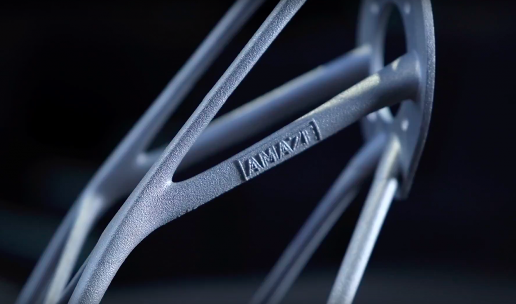 A 3D printed metal component featuring the AMAZE logo. Photo via AMAZE.