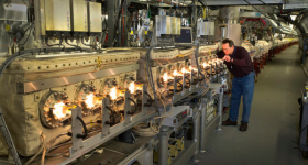 An engineer inspects the illuminated magnetic kickers of the synchrotron. Photo via Brookhaven National Laboratory.