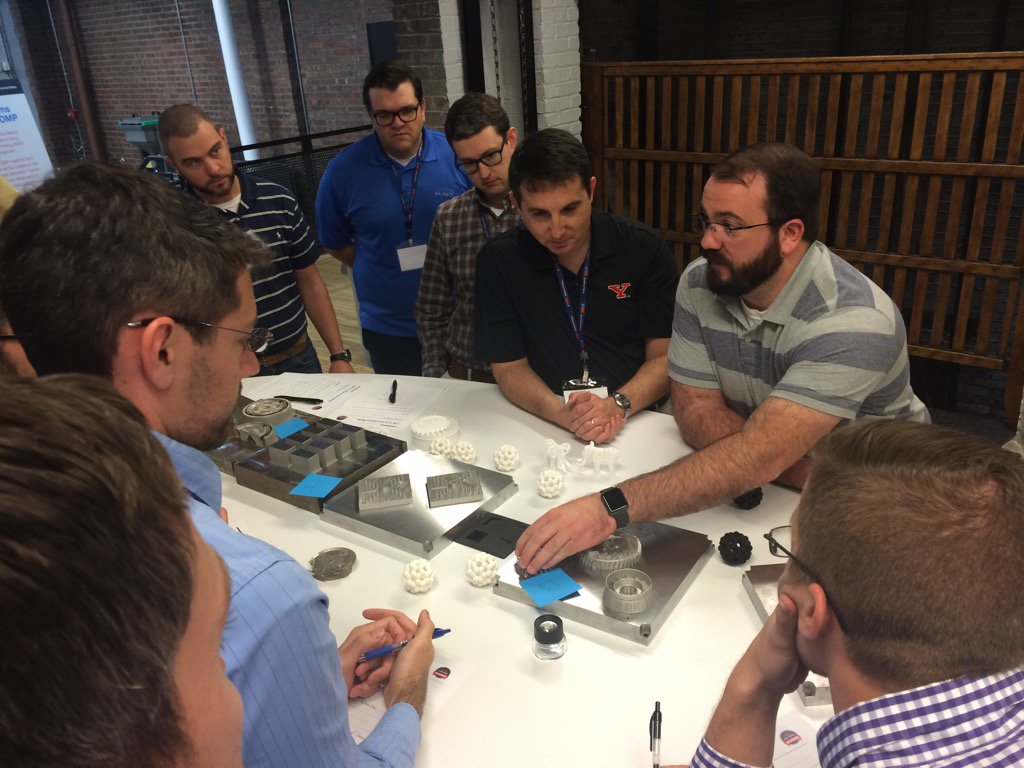 Students are taight about 3D printing in small groups as part of ACADEMI. Photo via America Makes.