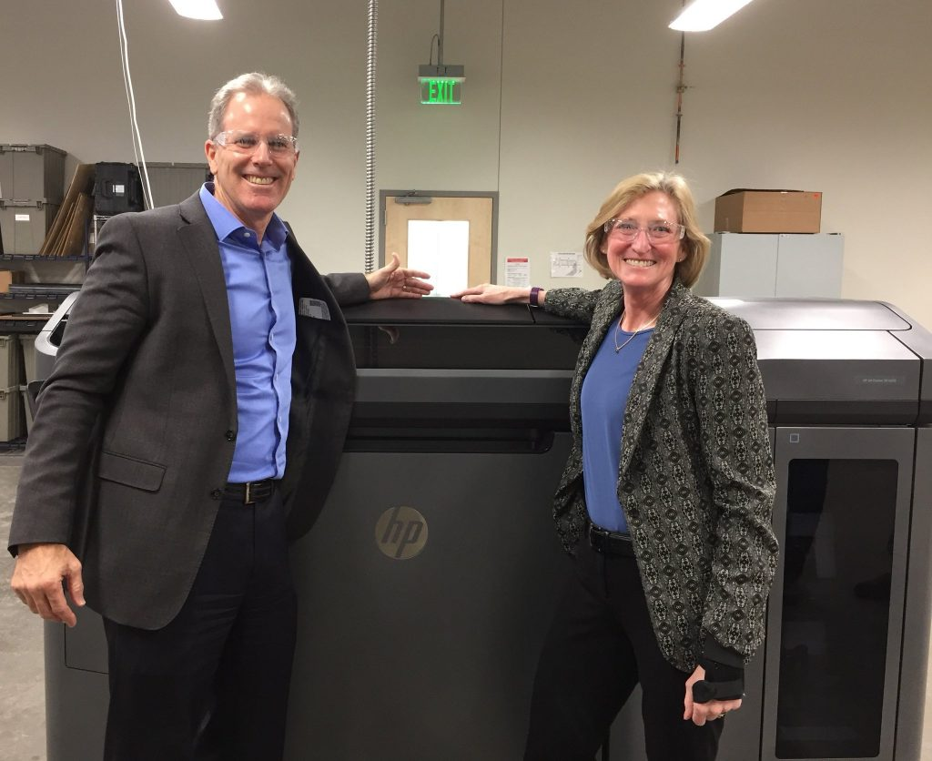 HP director of AM Stephen Nigro (L) with Proto Labs CEO Victoria Holt (R) with an HP Multi-jet Fusion 3D printer at the US facility. Photo via Proto Labs.
