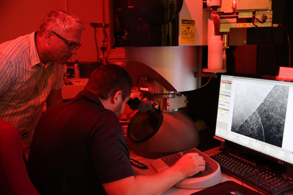 """LLNL materials scientist Joe McKeown looks on as postdoc researcher Thomas Voisin examines a sample of 3D printed stainless steel."" Photo by Kate Hunts/LLNL."