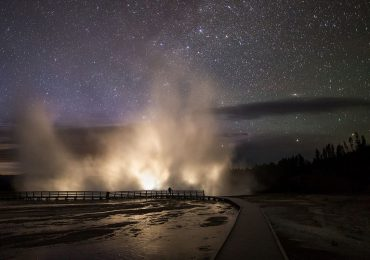 ellowstone National Park's Excelsior Geyser erupting at night - releasing methane and other gases into the atmosphere. Photo by Neal Herbert, National Park Service.