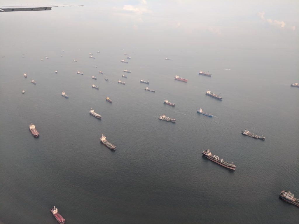 Cargo ships in the sea off the coast in Singapore. Photo by Michael Petch.