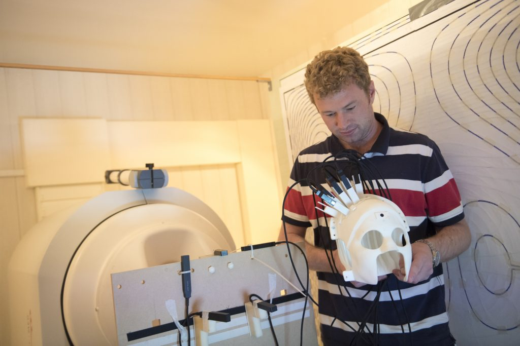 Dr. Matthew Brookes hold the helmet/headcast prototype. Photo via the University of Nottingham