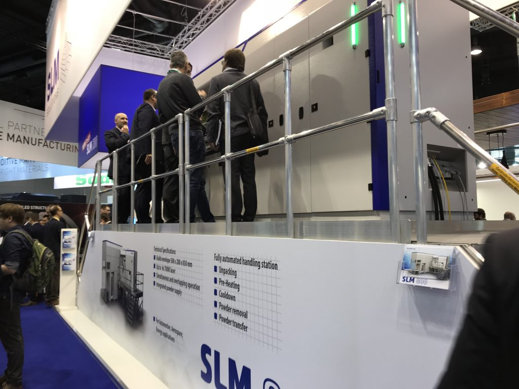 The large SLM 800 with a crown of visitors. Photo by Beau Jackson for 3D Printing Industry