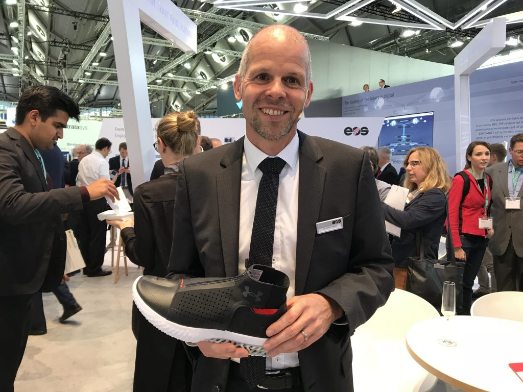 Adrain Keppler, CEO of EOS, holds a prototype sneaker product of a collaboration with Under Armour. Photo by Beau Jackson for 3D Printing Industry