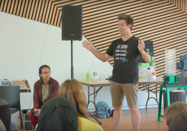 Lomman presenting GreenBatch's work at a school whilst wearing a 3D printed fabric T-shirt. Photo via GreenBatch.