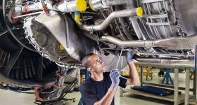 A GE engineer maintains the aircraft engines. Photo via GE.