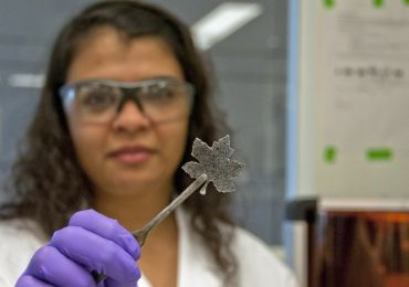UAlberta's Stella Mathews holds up a 3D printed maple leaf sample. Photo by Michael Brown