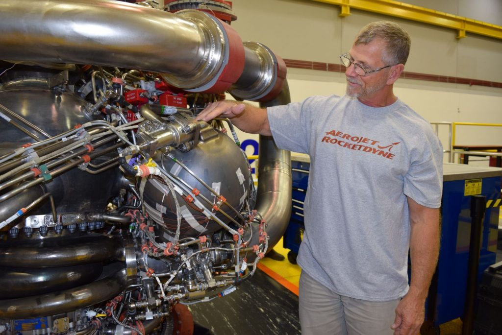 An Aerojet Rocketdyne technician inspects the 3D printed pogo accumulator assembly on an RS-25 development engine. Photo via Aerojet Rocketdyne
