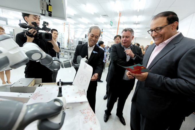 Innovation at HP's Smarc include the development of cobots for enhanced automation. Here Mr Iswaran receive a card written by a robotic arm at the center's grand opening. Photo via HP