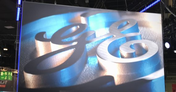 A metal GE logo at the GE Additive booth formnext 2017. Photo by Beau Jackson