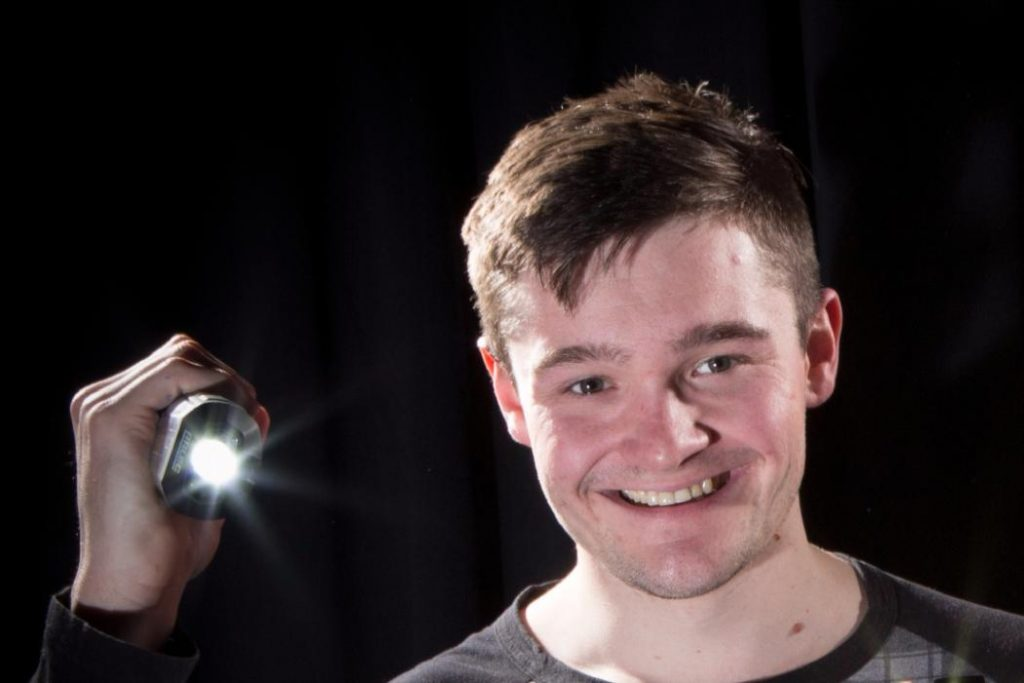 Logan Williams with a strobe light testing the effectiveness of the 3D printed lenses. Photo via UCC.