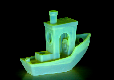 A glowing 3D printed Benchy boat - the benchmark test for FDM 3D printers. Photo via Matterhackers