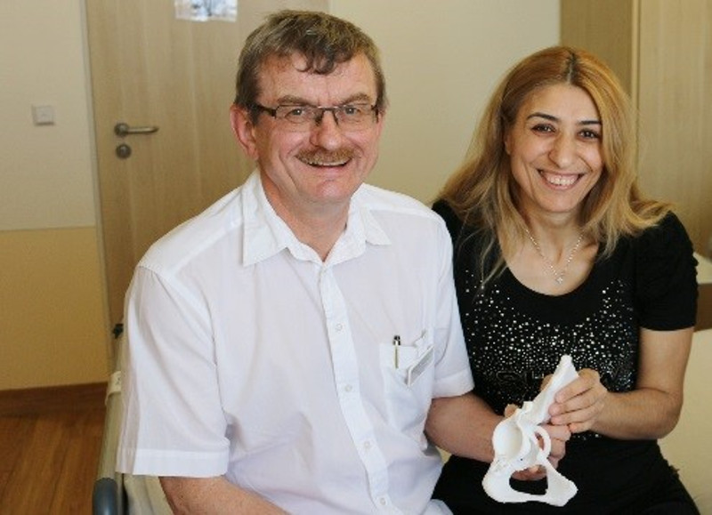 Dr. Burkhard Wippermann and his patient Antzelina Kesidi hold a prototype 3D printed hip and implant. Photo via Materialise