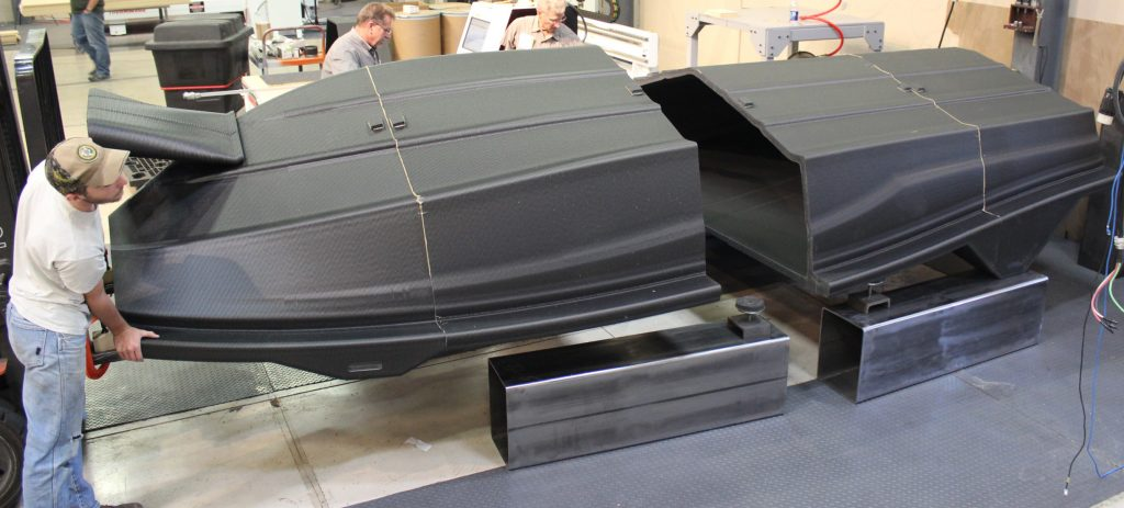 Piecing together the LSAM 3D printed hull pattern. Photo via JEC Group