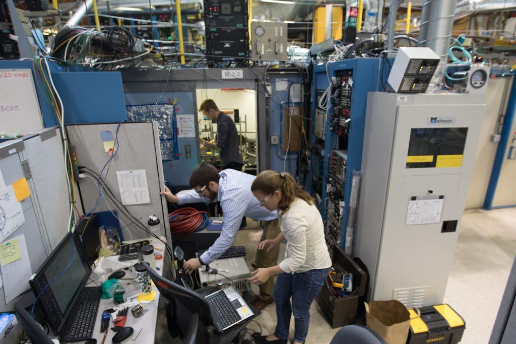"""SLAC staff scientist Johanna Nelson Weker, front, leads a study on metal 3-D printing at SLAC's Stanford Synchrotron Radiation Lightsource with researchers Andrew Kiss and Nick Calta, back."" Photo by Dawn Harmer, caption via SLAC"