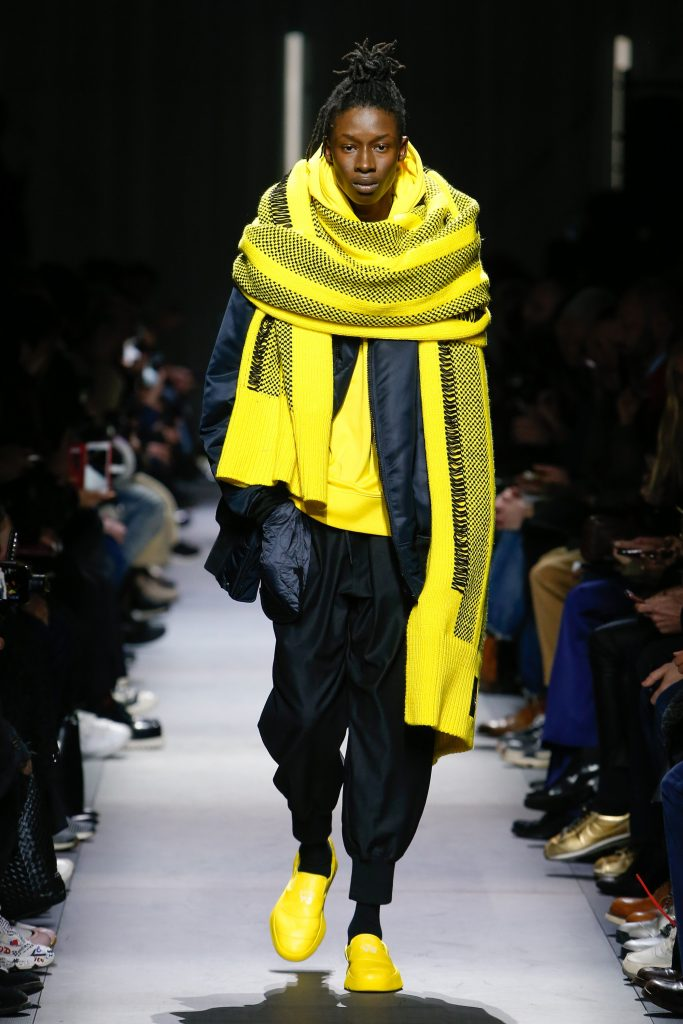 Y-3 Fall 2018 Menswear features huge yellow scarfs. Photo via Photo: Monica Feudi / Indigital.tv.