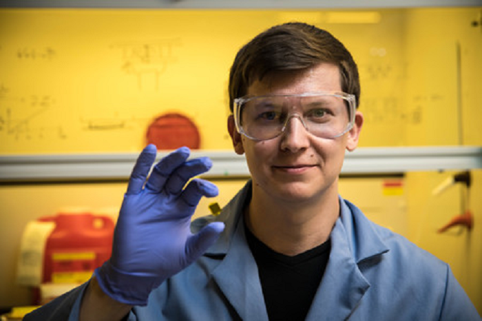 Greer Group researcher and lead author of the Caltech research paper Andrey Vyatskikh holds a slide that holds microscopic 3D printed nickel structures.
