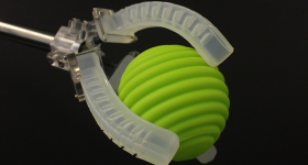 A soft robot gripper with embedded sensors that can sense movement, pressure, touch, and temperature grabbing a ball. Photo via Harvard SEAS.
