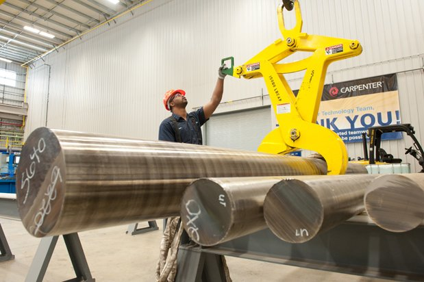 A Carpenter employee uses a lift to move solid steel alloy rods at a facility in Alabama. Photo via Carpenter Technology