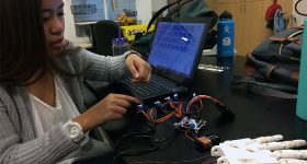 "GCU researcher Denise Delos Santos checking ""the connections of a 3D printed prosthetic hand, a project of the Research and Design Program's 3D printing biotechnology group."" Photo and captin by Lana Sweeten-Shults/Grand Canyon University"
