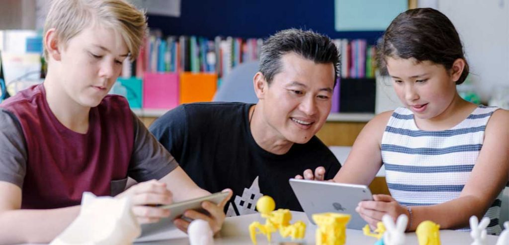 A teacher supervising 3D printing with young school students. Photo via GE.