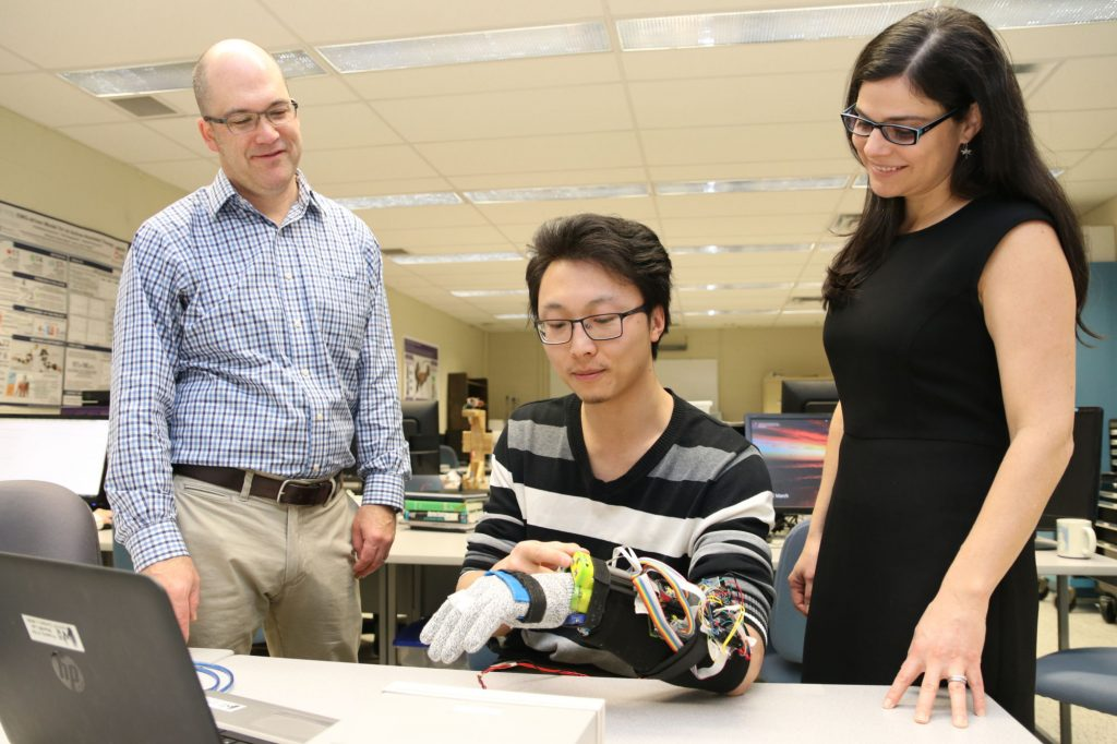 Ana Luisa Trejos examines the prototype tremor suppression glove worn by Yue Zhou. Photo via Western University.