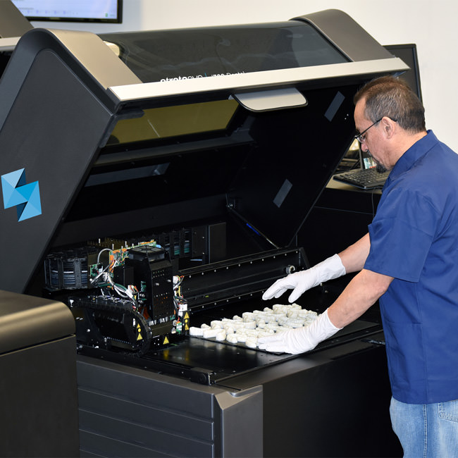 Inspecting dental molds in the Stratasys J700. Photo via Stratasys.