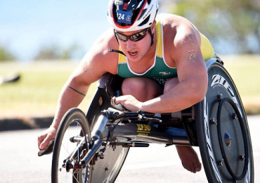 Scott Crowley wheelchair racing, with non-3D printed gloves. Photo via The Good Scout Facebook.